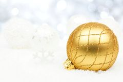 Gold and silver Christmas ornaments in snow with twinkling background stock image
