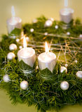 Gold and silver christmas wreath. Christmas wreath with silver lighted candles, ivy leaves and white pearls nad balls on green and golden background Royalty Free Stock Photo