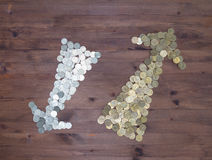 Gold and silver coins arrow on  wooden table Royalty Free Stock Image