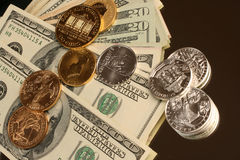 Gold and silver coins and paper money Stock Image