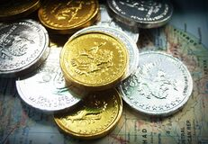 Gold and silver coins on world map Stock Photography