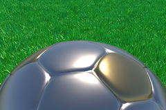 Gold And Silver Football. Realistic 3d rendering of a gold and silver football on green grass Stock Images