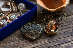 Gold and silver jewelry on wood table Stock Photos