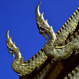 Gold & Silver Nagas on a Temple. Gold & Silver Nagas/Serpents adorn the gables on a Temple at Doi Suthep in Chiang Mai, Thailand, witha clear blue sky Royalty Free Stock Image