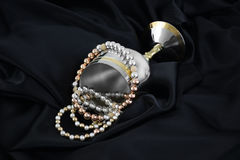 Gold, silver and pearls on a black silk Royalty Free Stock Photo