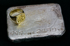 Gold and Silver - Precious Metals. Large gold nugget ring and silver bullion bar (ingot) - Precious Metals Stock Photography