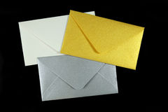 Gold, silver and white envelopes on black Royalty Free Stock Images