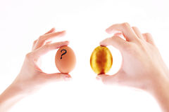 Gold and simple egg in hands. Isolated on white Royalty Free Stock Photography