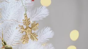 Gold snowflake and decor ball hanging on white Christmas tree with bokeh lights decoration at background,Holiday celebration conce stock footage