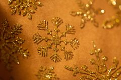 Gold snowflake glitter pattern on brown royalty free stock image