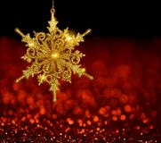 Gold Snowflake on Red Blur Background. Sparkling gold snowflake ornament on a red and black bokeh background royalty free stock photography