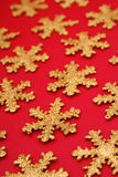 Gold snowflake shapes. On red background Stock Image