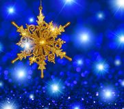 Gold Snowflake Star on Blue Stars Background. Gold glitter snowflake ornament on a blue stars and bokeh background with copy space stock image