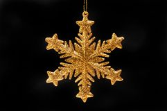 Gold snowflake star. Gold glitter Christmas snowflake star decoration isolated against white Royalty Free Stock Photo