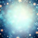 Gold snowflakes frame. Sparks and snow on blue glare defocused background. Winter blurred texture. Night holiday party empty Stock Photos