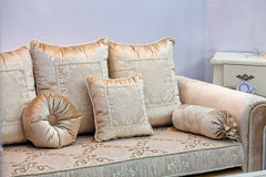 Gold sofa with pillows Stock Photography