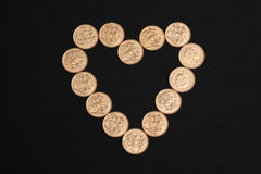Gold sovereign coins in heart shape Stock Photo