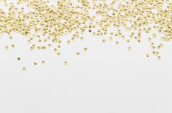 Gold sparkle rain framed at corners on white table isolated background. Top view with copy space.  stock photography