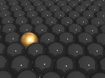 Gold sphere in row of black spheres Stock Image