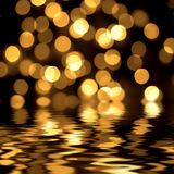 Gold spots bokeh background. Reflected in the water Royalty Free Stock Images