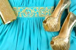 Gold-Stöckelschuhe, Handtasche und blaues Kleid mit Gold-acce Stockbild
