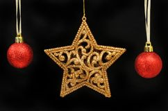Gold star and baubles against black Royalty Free Stock Photography
