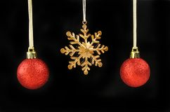 Gold star and baubles. Gold snowflake Christmas star decoration with red baubles isolated against black Stock Image