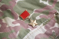 The Gold Star medal is a special insignia that identifies recipients of the title Hero in the Soviet Union on Soviet camouflag Royalty Free Stock Images