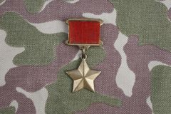 The Gold Star medal is a special insignia that identifies recipients of the title Hero in the Soviet Union on Soviet camouflag Royalty Free Stock Photo