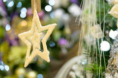 Gold star ornament hanging from Christmas tree. Sparkling gold star ornament hanging from Christmas tree Royalty Free Stock Image