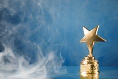 Gold star trophy in smoke
