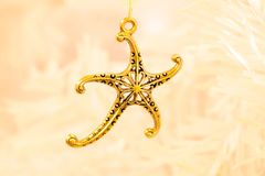 Gold starfish  pendant. A close up  of a gold coloured starfish  pendant on the branch a white Christmas tree Royalty Free Stock Photos