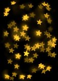 Gold stars background. Gold stars bokeh background on black Stock Images