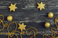 Gold stars and Christmas balls on a black wooden background. Gold stars and Christmas balls on a black wooden background Royalty Free Stock Images