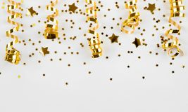 Gold stars confetti and curled ribbons isolated on white background.  Royalty Free Stock Images
