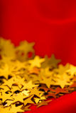 Gold stars on red fabric. macro Royalty Free Stock Photo
