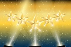 Gold 5 Stars in Spotlights. Spotlight shining on gold 5 stars and gold background with sparks. Five stars in light Royalty Free Stock Photography