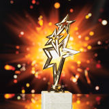Gold stars trophy against shiny background Stock Images