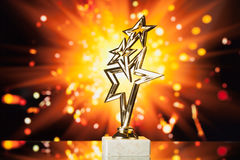 Gold stars trophy against shiny background Stock Image
