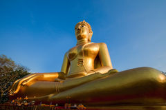 Gold statue of the Buddha. Against the blue sky Stock Images