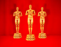 Gold statues on red. Royalty Free Stock Photography