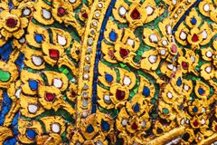 Gold stucco design of native thai style on the Wall in Buddhist Royalty Free Stock Photo