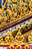 Gold stucco design of native thai style on the Wall in Buddhist Royalty Free Stock Image