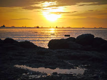 Gold sun light and stone seaside in Thailand Stock Photo