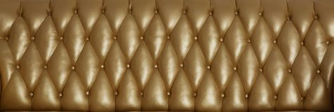 Gold surface of the leather back. The gold surface of the leather back of the vintage couch stock image
