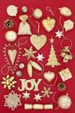 Gold Symbols of Christmas. Gold christmas symbols with tree decorations and baubles over red background Stock Image