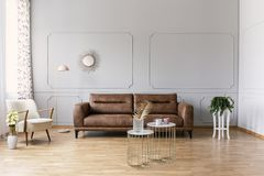 Gold tables in front of leather couch in grey flat interior with yellow flowers and armchair. Real photo stock photos