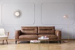 Gold tables in front of leather sofa in grey elegant living room interior with mirror and lamp. Real photo stock images
