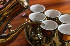 Gold tea pot. And cup focus Royalty Free Stock Photos