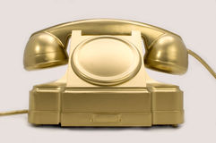 The gold telephone. The telephone of gold colour on a white background Stock Images
